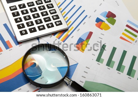 Calculator and magnifier on a business background - stock photo