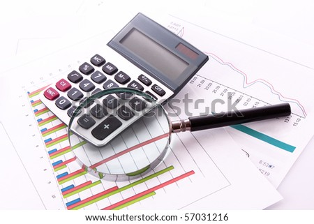 calculator and magnifier on chart background