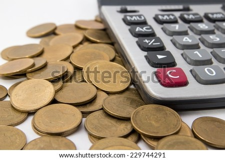 Calculator and many gold coins. - stock photo