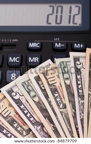 Calculator and money of $5-$20 banknotes. 2012 happy new year. - stock photo