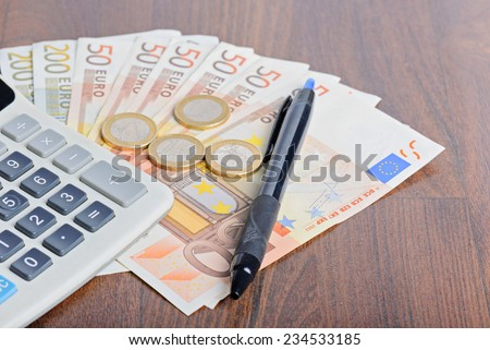 Calculator and money on the table - stock photo