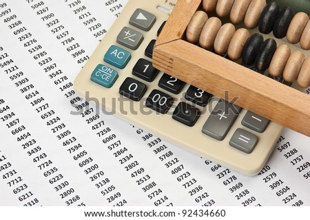 calculator and old wooden abacus on the background working papers - stock photo