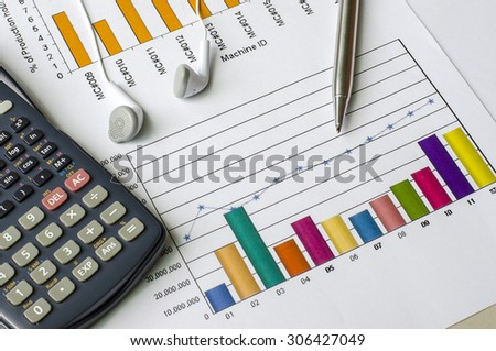 Calculator and pen and earphone on graphs paper - stock photo