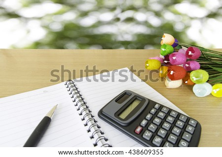 calculator and pen and notebook on wood table - stock photo