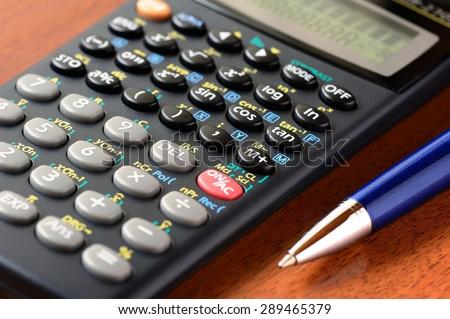 Calculator and pen, closeup, shallow DOF - stock photo