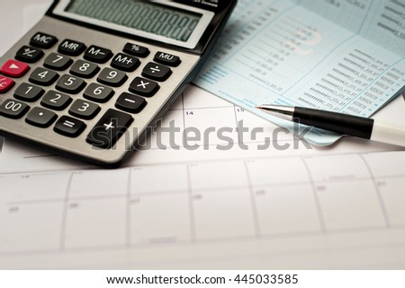 Calculator and pen on a passbook and calendar background