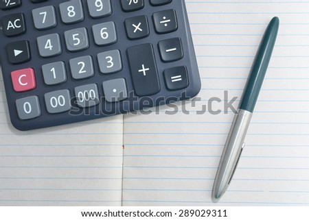 calculator and pen on blank notebook.