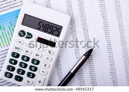 Calculator and pen on calculates - stock photo
