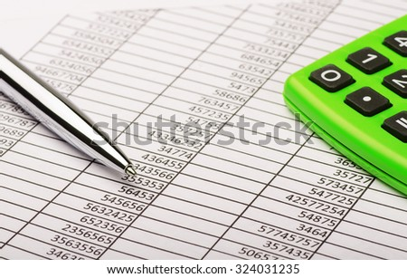 Calculator and pen on financial report  - stock photo