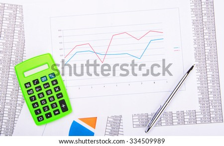 Calculator and pen on financial report with diagram - stock photo