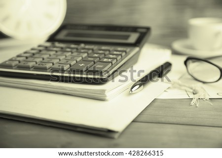 Calculator and pen on notebook and cup of coffee and glasses on table - stock photo