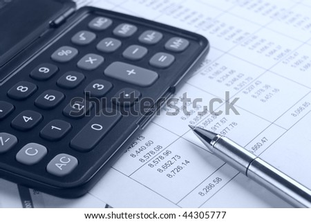 calculator and pen on report.