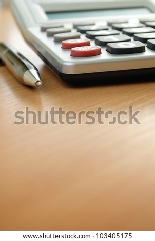 calculator and pen on the table and place for text