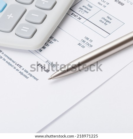 Calculator and pen over some receipt - 1 to 1 ratio - stock photo