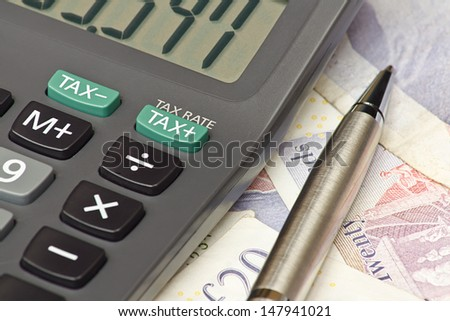 Calculator and pen symbolizing completing your personal Income tax returns for the inland revenue service or IRS - stock photo