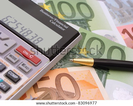 Calculator and pen with money in the background - stock photo