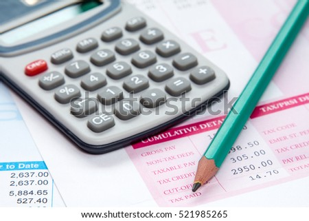 Calculator and pencil on the statement of payroll details