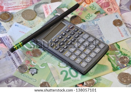 Calculator and pencil over international currencies - stock photo