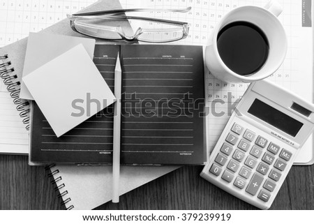 calculator and planner on the wooden table with black and white color concept - stock photo