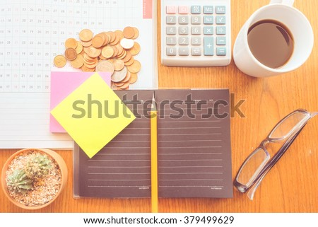 calculator and planner on the wooden table with vintage color concept - stock photo