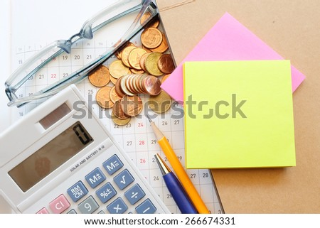 calculator and planner on wooden table with coin - stock photo