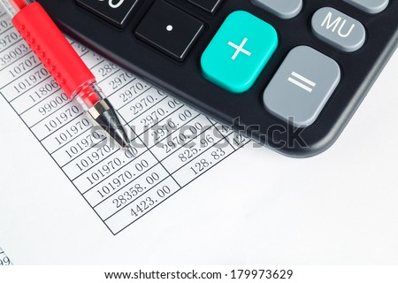 calculator and red pen on a digital report ,financial check concept  - stock photo