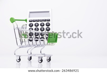 Calculator and shopping trolley over white background - stock photo