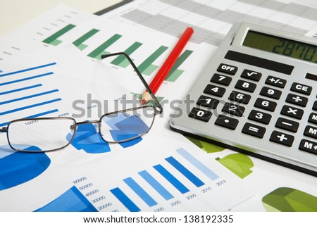Calculator and spectacles on a business background - stock photo