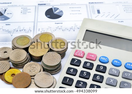 calculator and stack of coins on written graph of white paper