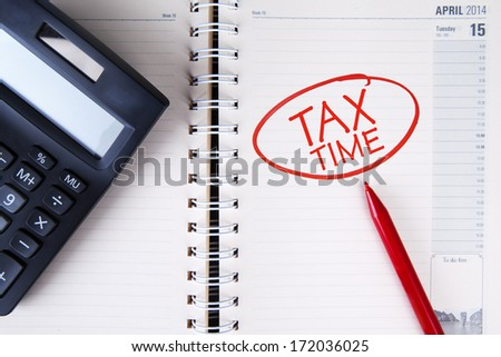 Calculator and tax time written on the agenda - stock photo
