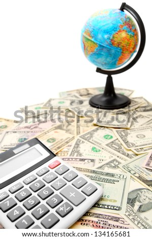 Calculator and the globe on dollars. - stock photo