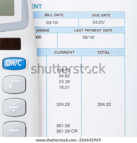 Calculator and utility bill next to it - close up shot - stock photo