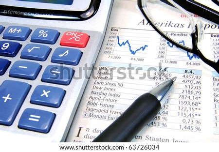 Calculator, ball-pen and glasses on top of a stock exchange report - stock photo