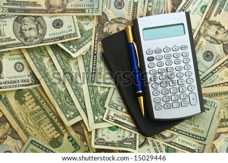 calculator, banknotes and pen on top - stock photo