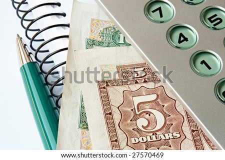 Calculator, banknotes, pen and notebook. The five and ten dollar banknotes were issued by HSBC HK in 1975 and 1981, respectively.