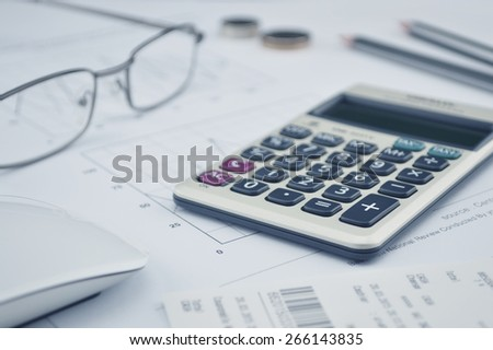 Calculator button plus, glasses coin pencil and mouse on graph paper background - stock photo