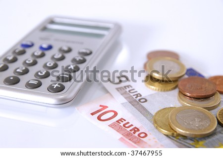 Calculator, coins and bills on white