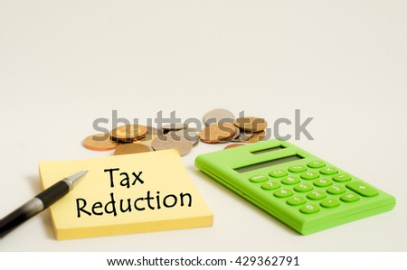 Calculator, coins and yellow note with word tax reduction on white background. Financial concept. - stock photo