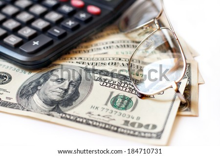 Calculator, dollars and glasses  - stock photo