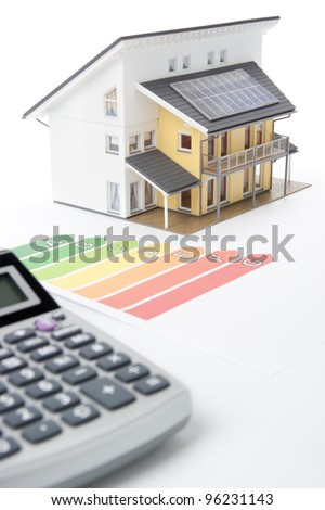 Calculator, energy efficiency rating graph and model of the active house.  Focused oh graph and part of the house. - stock photo