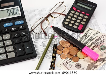 Calculator, glasses, pen, dollars and coins on the background papers to the amounts - stock photo