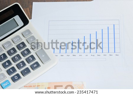 Calculator, graphyc and banknotes on the table - stock photo