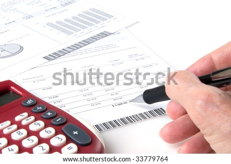 Calculator, hand holding mechanical pencil, investment statement, Shallow depth of field, focus on pencil point - stock photo