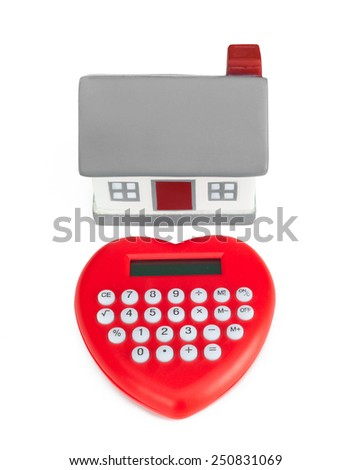 Calculator heart shaped and miniature house. Concept of purchase or mortgage. - stock photo