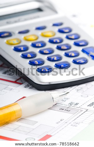 calculator lying on a plan of a house with a pen - stock photo