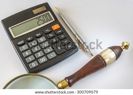 Calculator,Magnifying Glass, And Ballpoint Pen On White Background