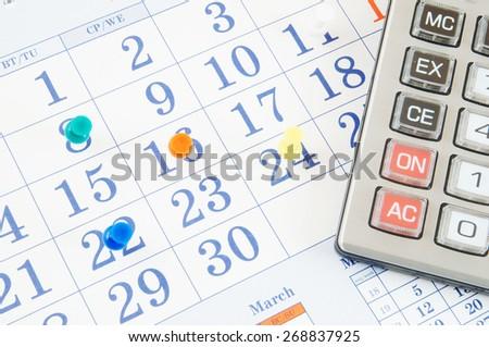 Calculator on calendar with push pins - stock photo