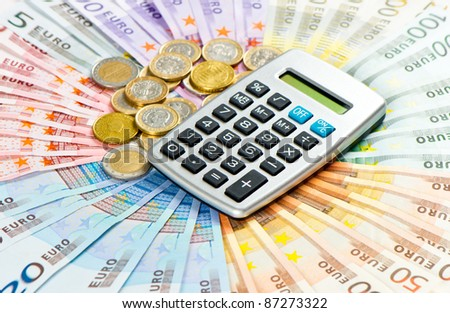 calculator on euro coins and banknotes background