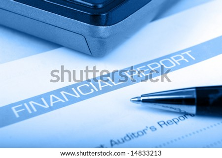 calculator on financial statement with blue overlay and shallow Depth of field - stock photo