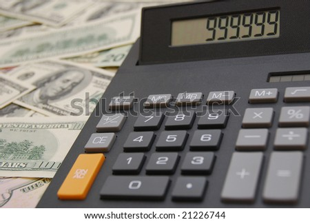 Calculator on money background of $100 and $50 banknotes